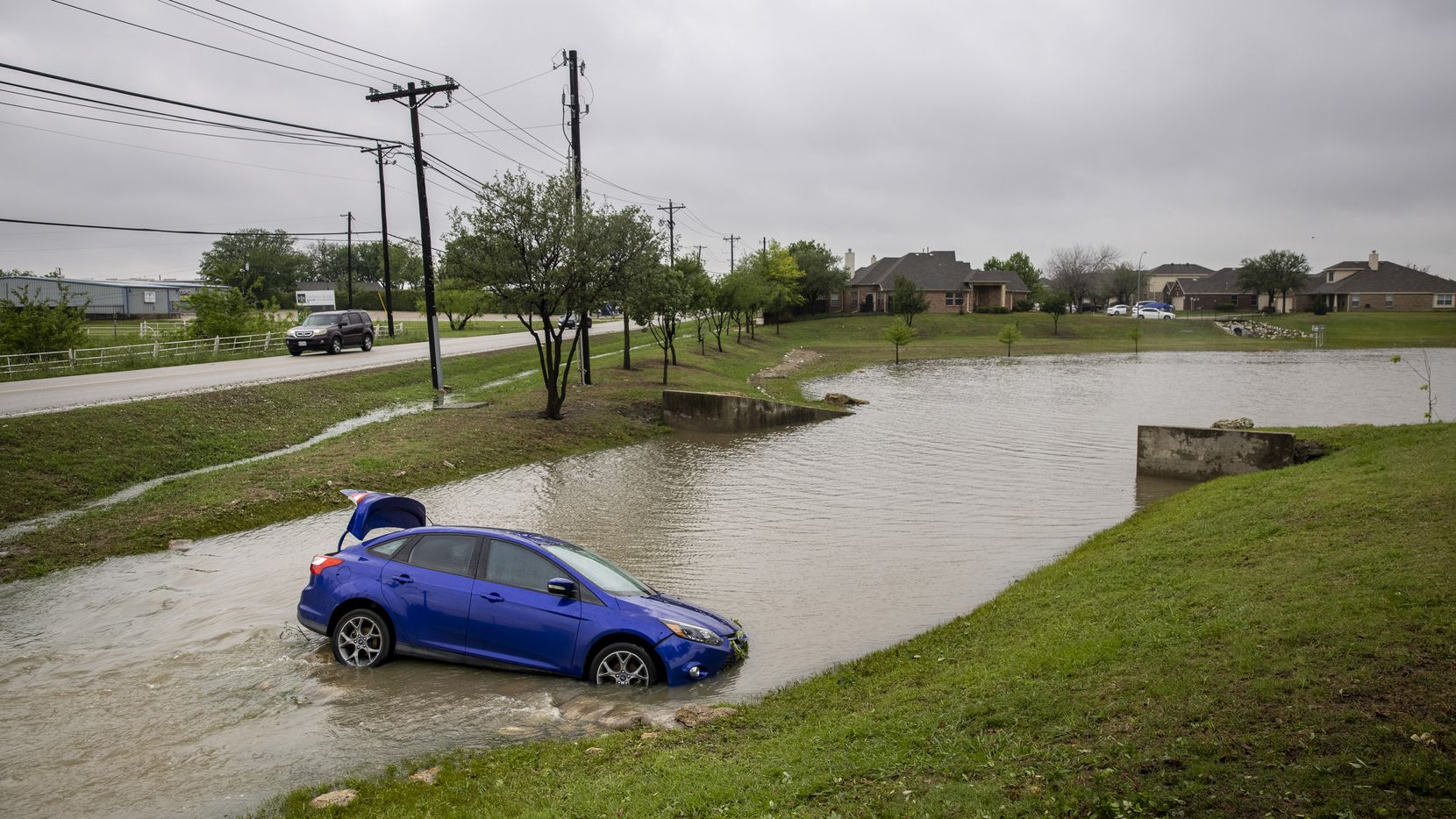 Following a severe storm Thursday night, water rushes past a car whose drive had landed in the creek at The Villages of Woodland Springs in Keller, Texas, on Thursday, April 29, 2021. A neighbor said the driver couldn't see where the turn was in the midst of the storm, and added that the driver was not seriously injured.