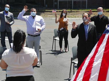 Varias personas prestan juramento para convertirse en ciudadanos estadounidenses afuera del edificio del Servicio de Ciudadanía e Inmigración el jueves 4 de junio de 2020, en Lawrence, Massachusetts.