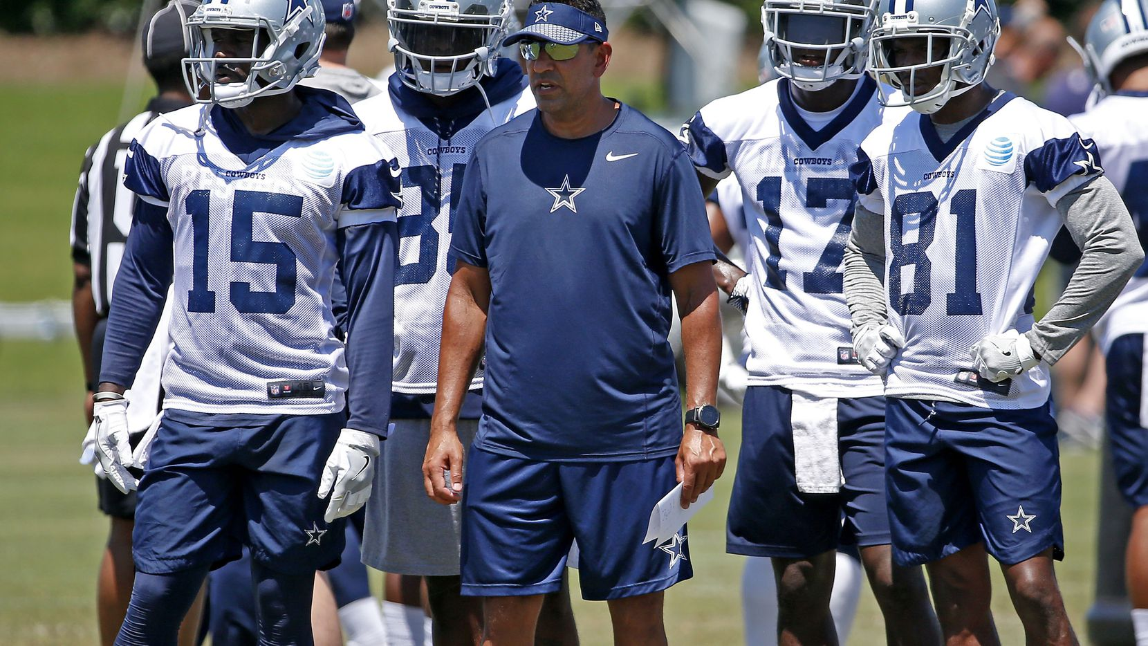 Dallas Cowboys wide receiver coach Sanjay Lal, center, is surrounded by his players Deonte Thompson (15), K.D. Cannon (81), Allen Hurns (17) and Noah Brown (85) during OTA practice at the Star in Frisco, Texas, Wednesday, May 30, 2018. (Jae S. Lee/The Dallas Morning News)