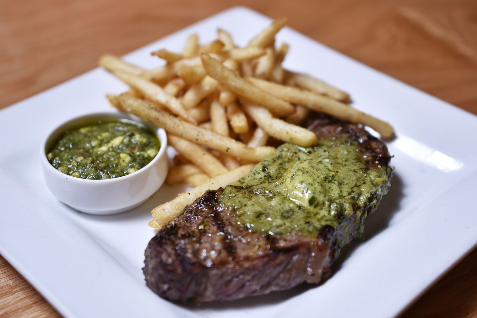 The $22 steak frites dish is a New York strip topped with avocado-herb butter and fries.