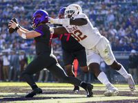 TCU Horned Frogs quarterback Max Duggan (15) avoids a safety attempt by Texas Longhorns defensive lineman Malcolm Roach (32) during the second quarter of an NCAA football game between the University of Texas and TCU on Saturday, October 26, 2019 at Amon G Carter Stadium in Fort Worth.