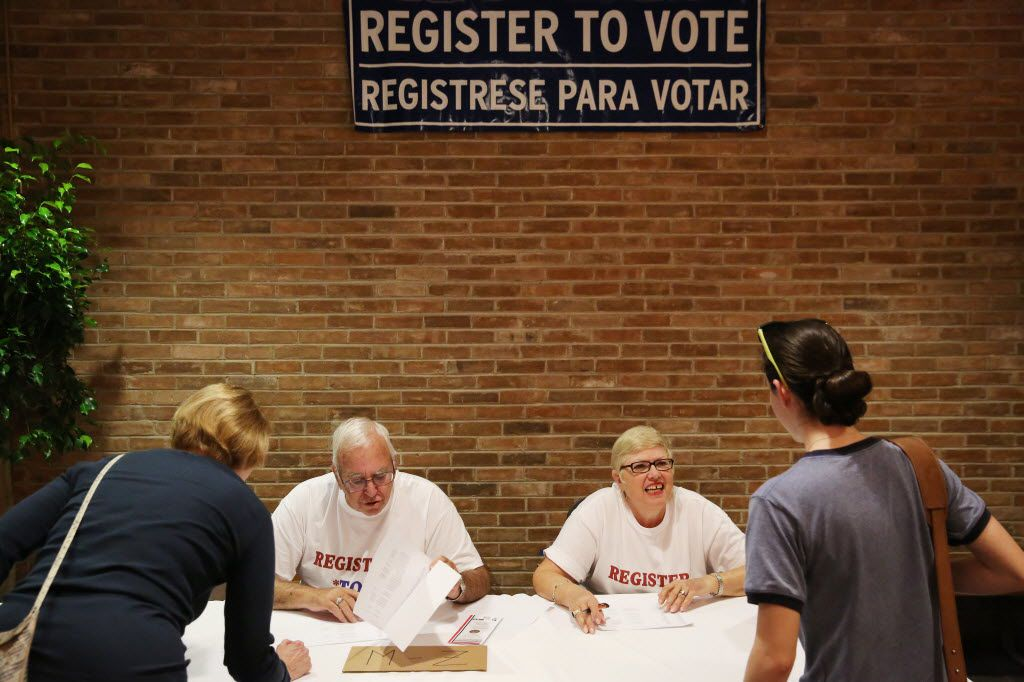 Art Kaplan (left), and his wife, Roz Kaplan, of Richardson, Texas, check-in guest before a deputy voters registrar class.
