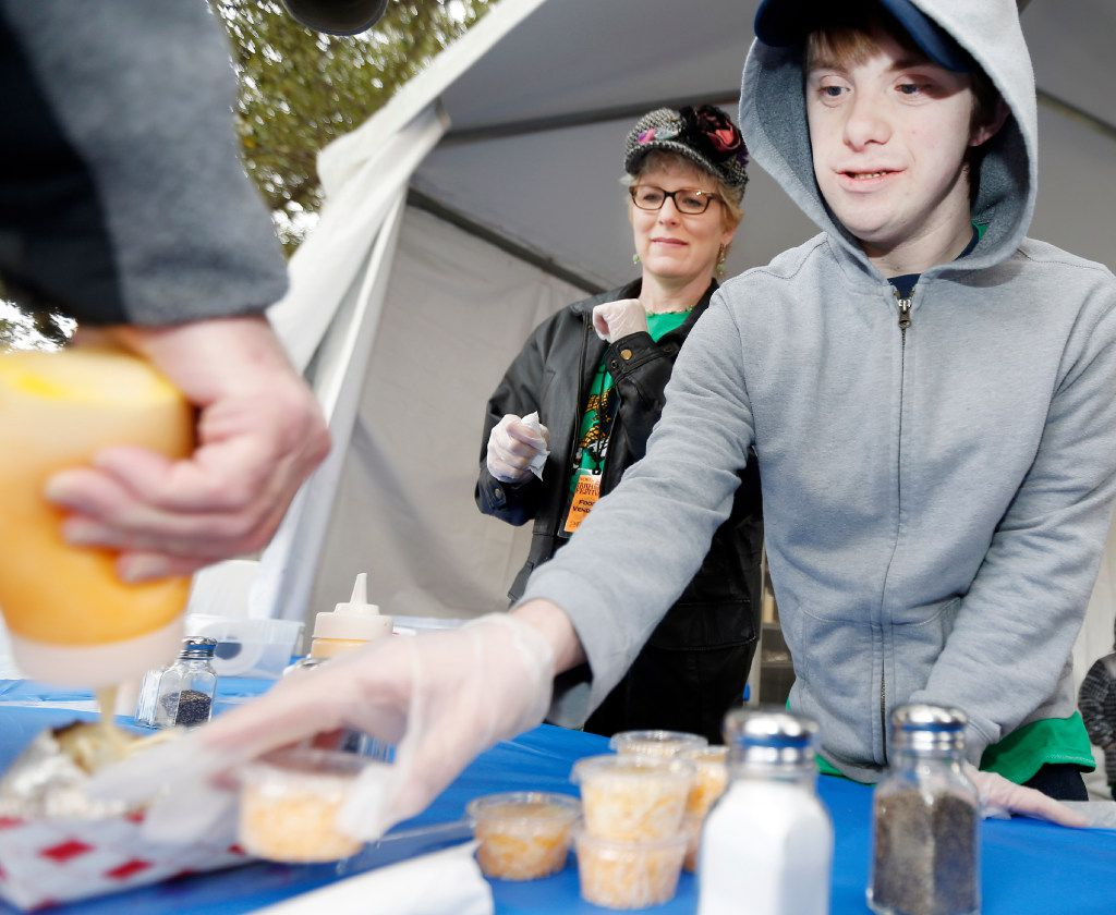 Erika Burkhardt, left, looks on as Scots Cafe student Chris Wheeler serves Karl Neumann, far left, during the North Texas Irish Festival at Fair Park in Dallas, Saturday, March 4, 2017. Scots Cafe is a Highland Park ISD transitional program for special needs students that teaches how to cook and serve food. (Brandon Wade/Special Contributor)