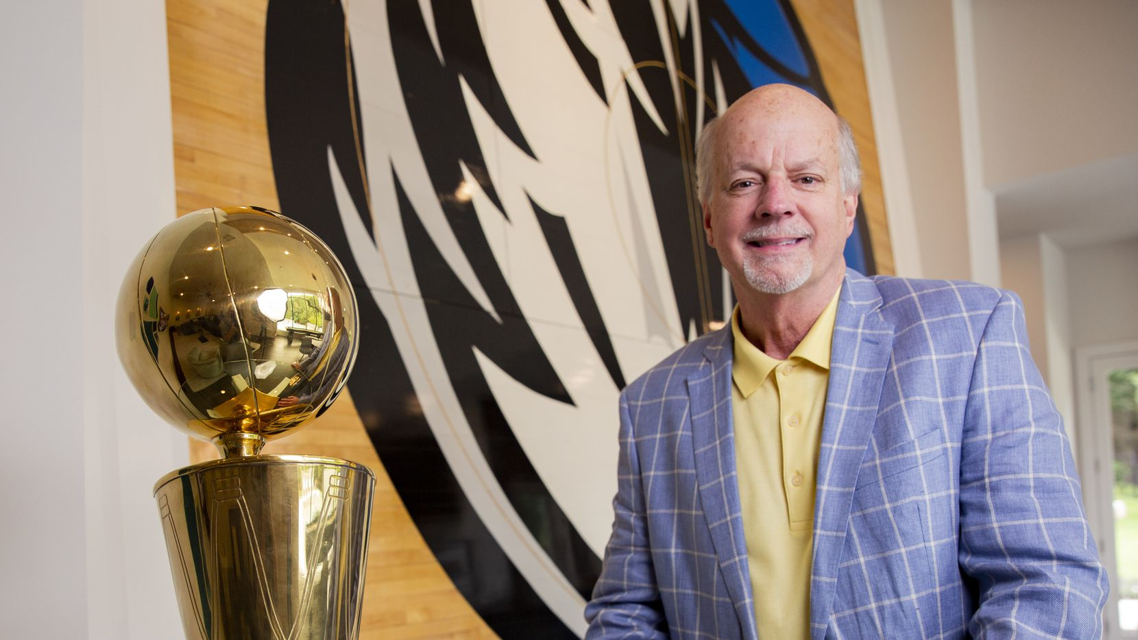Mavericks super fan Mark Thompson, owner of Smith-Thompson security company, poses in front of the center area of the hardwood floor from the 2011 NBA Finals on his wall and his replica of the championship trophy (given to him by Dirk Nowitzki) at his home on Wednesday, June 9, 2021, in Fairview.