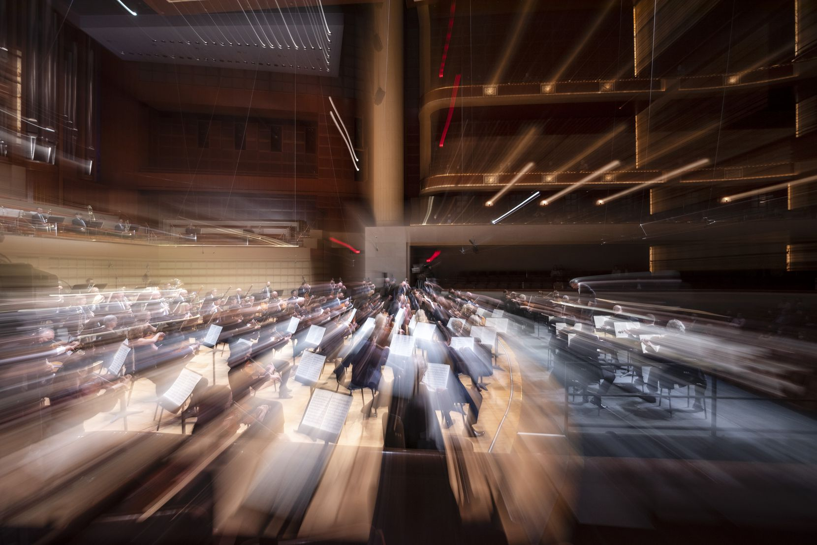 """A slow camera shutter shows musicians with the Dallas Symphony Orchestra and New York Metropolitan Opera Orchestra during a Friday night performance of Mahler Symphony No. 1 in D Major, """"Titan."""""""