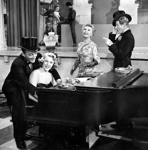 """Rosemary Clooney, at piano, with Bing Crosby (left) and Vera-Ellen and Danny Kaye in a scene from the 1954 movie version of """"White Christmas."""""""