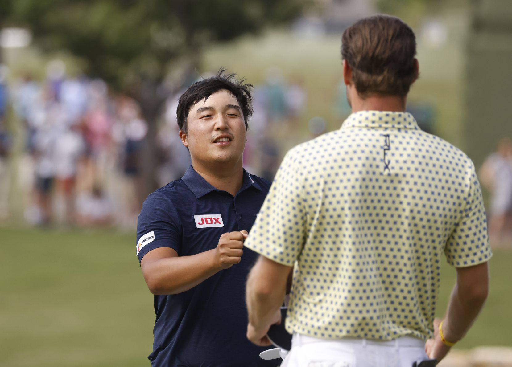 Kyoung-Hoon Lee bumps fists with Doc Redman after finishing on the 18th hole during round 3 of the AT&T Byron Nelson  at TPC Craig Ranch on Saturday, May 15, 2021 in McKinney, Texas. (Vernon Bryant/The Dallas Morning News)