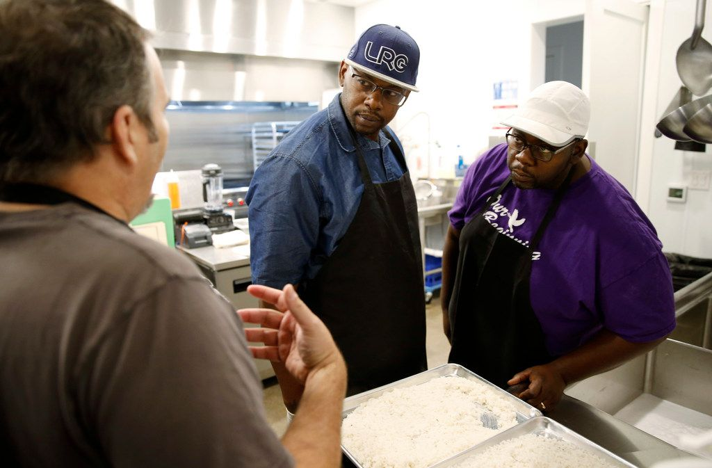 Chef Mike Noyes, left, talks to Derrick Runnels, center, and brother Darrell Runnels about the rice that was made using two different methods of cooking in the kitchen at The Market at Bonton Farms in Dallas. The Runnels brothers are from the Bonton area.