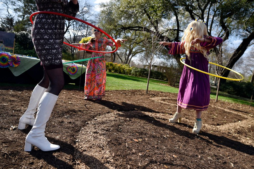 Arboretum staff, from left, Krista Bruton, Lise Takacs, and Megan Proska used hula hoops during an event promoting the Dallas Blooms: Peace, Love and Flower Power, at the Dallas Arboretum.