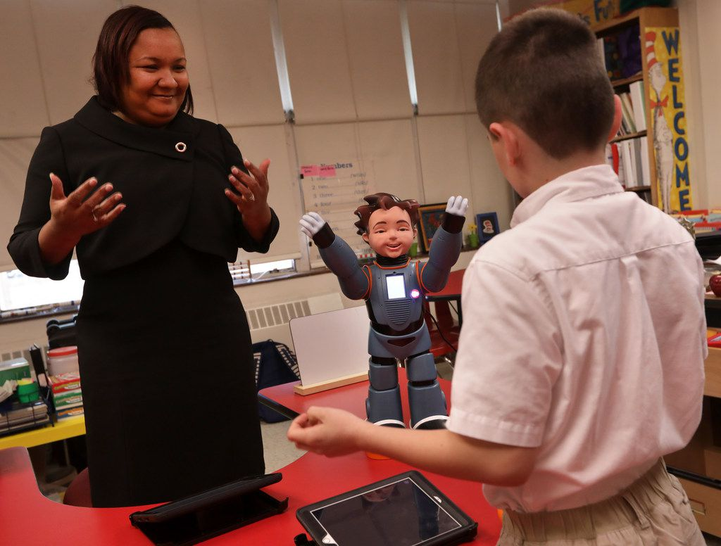 Karol Henderson (left)  and 7-year-old Maxwell Cowles dance with Milo the interactive robot during a class at Tom C. Gooch Elementary School in Dallas. (Jason Janik/Special Contributor)