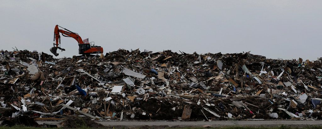 In this Friday, Sept. 29, 2017 photo, an excavator is used to move a mountain of debris created in the wake of Hurricane Harvey, Port Aransas, Texas. The storm damaged or destroyed 80 percent of local homes and businesses and arrived just before Labor Day, wiping out the lucrative summer season's final weeks. (AP Photo/Eric Gay)