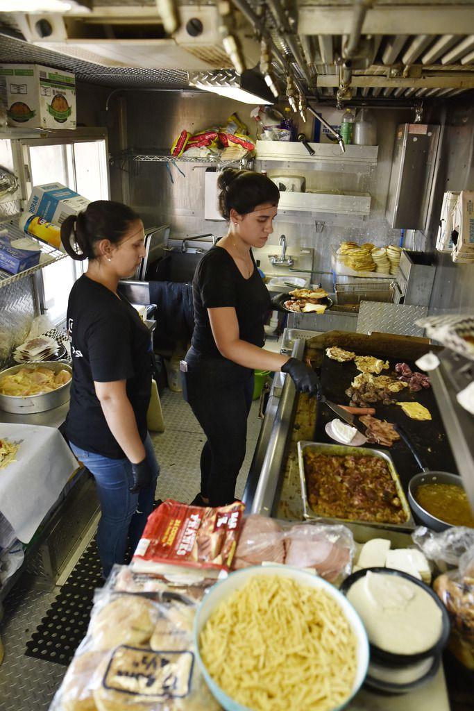 Dariela Cuadrado (izq.), prepara comida junto a su asistente Fabiola Sánchez, en el food truck Sabor Venezolano Express, en Carrollton.