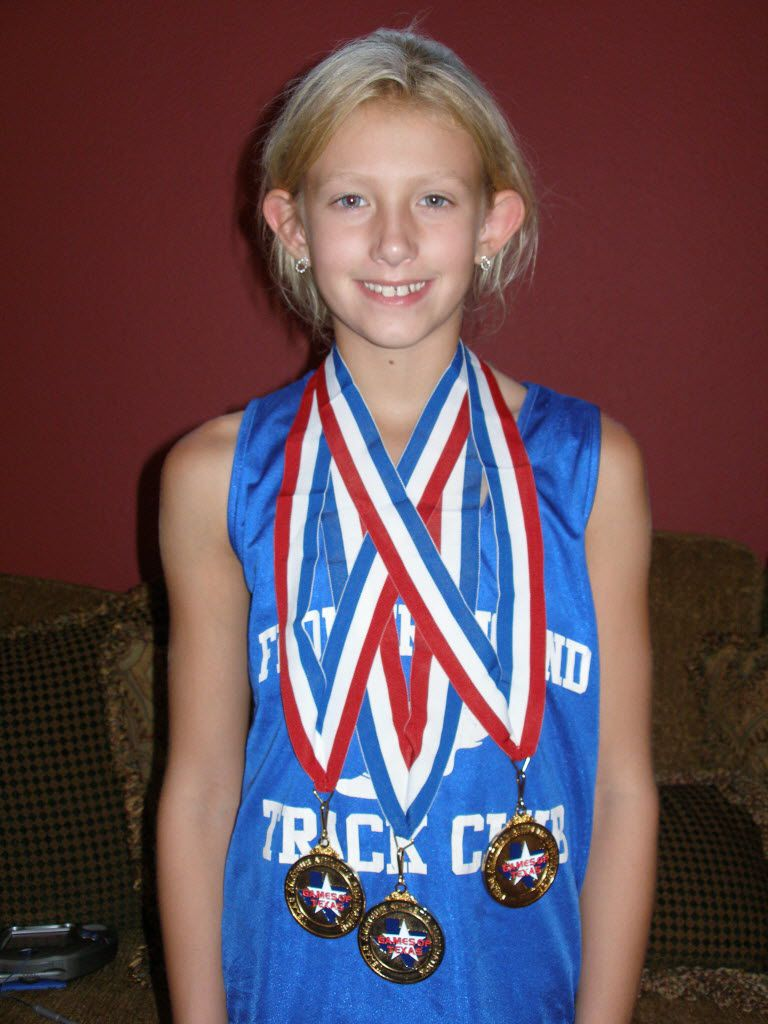 """Lauren Cox at age 8 poses with medals after winning the 50m dash, 100m dash and high jump at the state track meet in Waco. Her high jump mark was 4'2""""."""