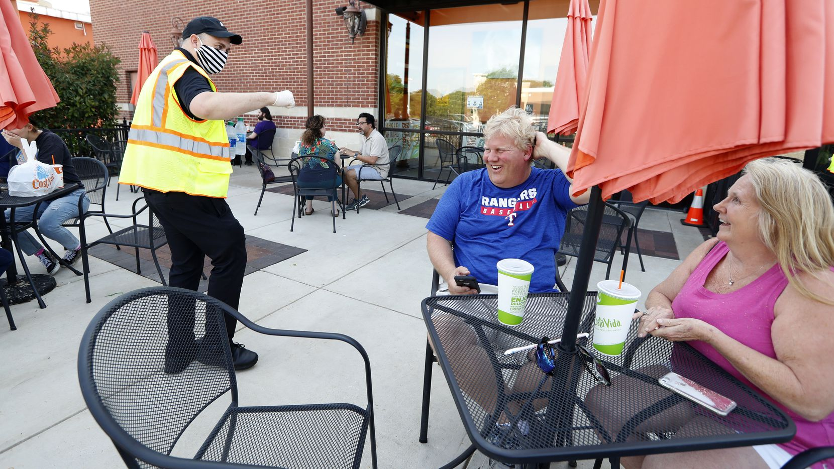 Jay Norman talks with Chad Steenwyk and his wife, Glenda, as the two dine outdoors on the patio at a restaurant in Colleyville.