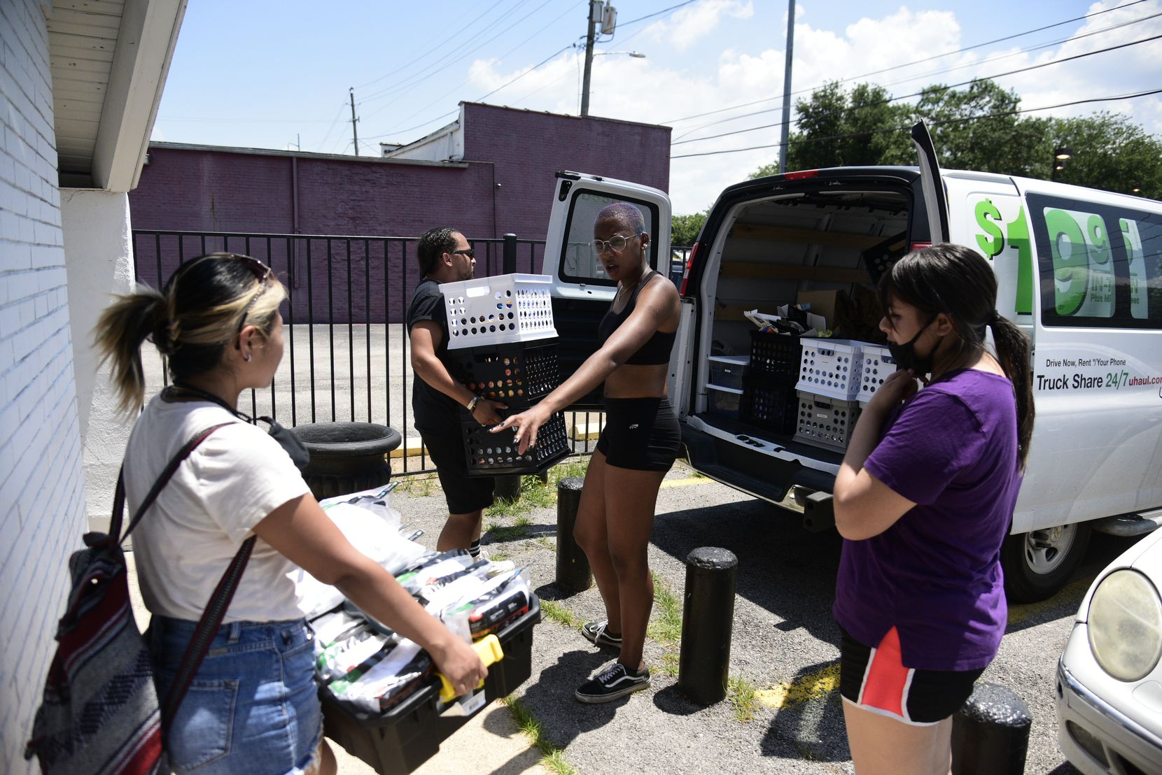 Patrick Averhart, left, and Danielle Carty load a supply van and direct volunteers at Sunny South Nutrition in South Dallas before supply distribution for Feed the People Dallas, a mutual-aid organization, on June 17, 2021.