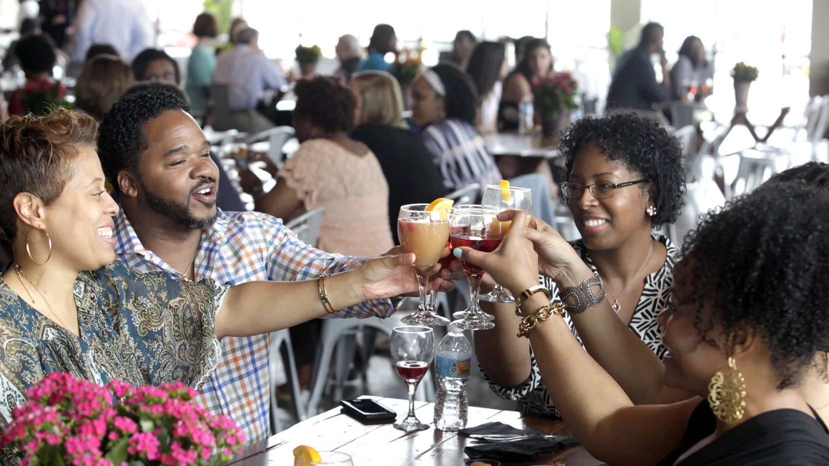 Friends raise a glass at Waffle Wars, a Savor Dallas event, at 3015 Trinity Groves in Dallas in April 2016.