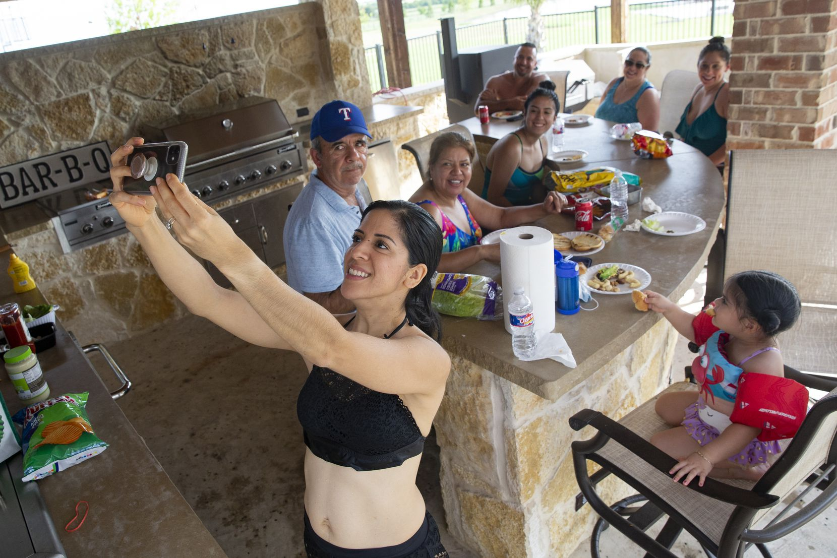 "Imelda Mendoza takes a selfie with her family as they eat after swimming in a backyard pool they rented using the Swimply app on July 26, 2020 in Waxahachie. ""Since we can't go on vacation, this is our little getaway,"" Jessica Banda, Adriana's sister-in-law, said."