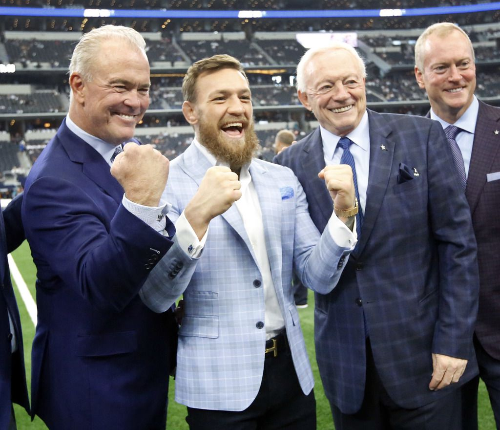MMA fighter Conor McGregor of Ireland (second from left) throws up his fists with Stephen Jones (left) as they pose with owner Jerry Jones and Jerry Jones Jr. (right) at AT&T Stadium in Arlington, Texas, Sunday, October 14, 2018. The Cowboys are facing the Jacksonville Jaguars.