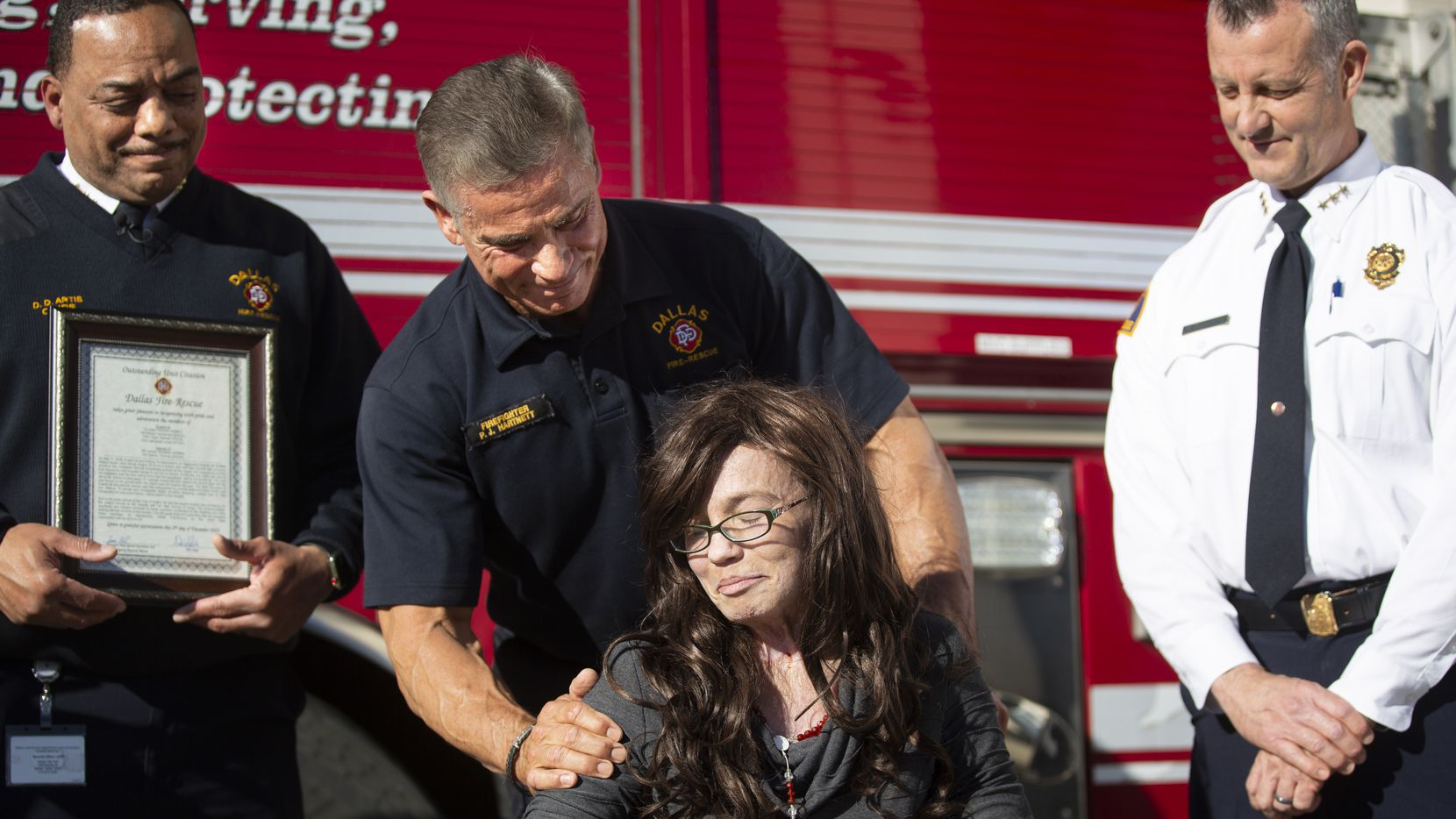 Dallas Fire-Rescue firefighter Peter Hartnett and Danyeil Townzen share a moment during a press conference honoring Hartnett and the rest of the crew riding DFR Engine 28 for saving Townzen's life last year. (Juan Figueroa/ The Dallas Morning News)