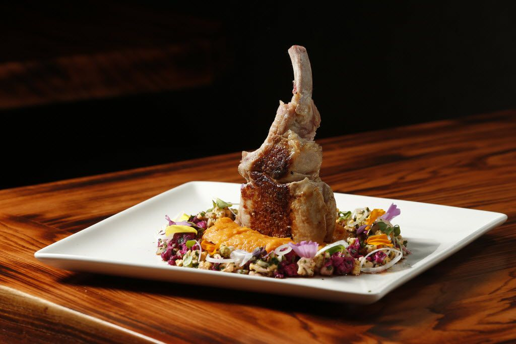 A bone-in pork chop with sweet potato puree is ringed with vegetables escabeche.