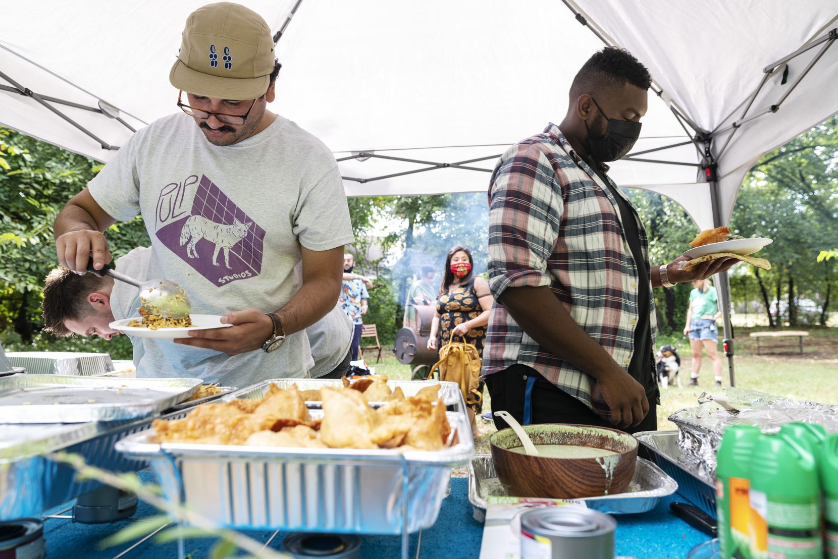 Daniel F., 28, left, and Abdelhalim Awadalla, 28, serve themselves food during a PunjabiTex BBQ popup, conducted by Chef Usama Khalid, at Sweet Pass Sculpture Park in Dallas.