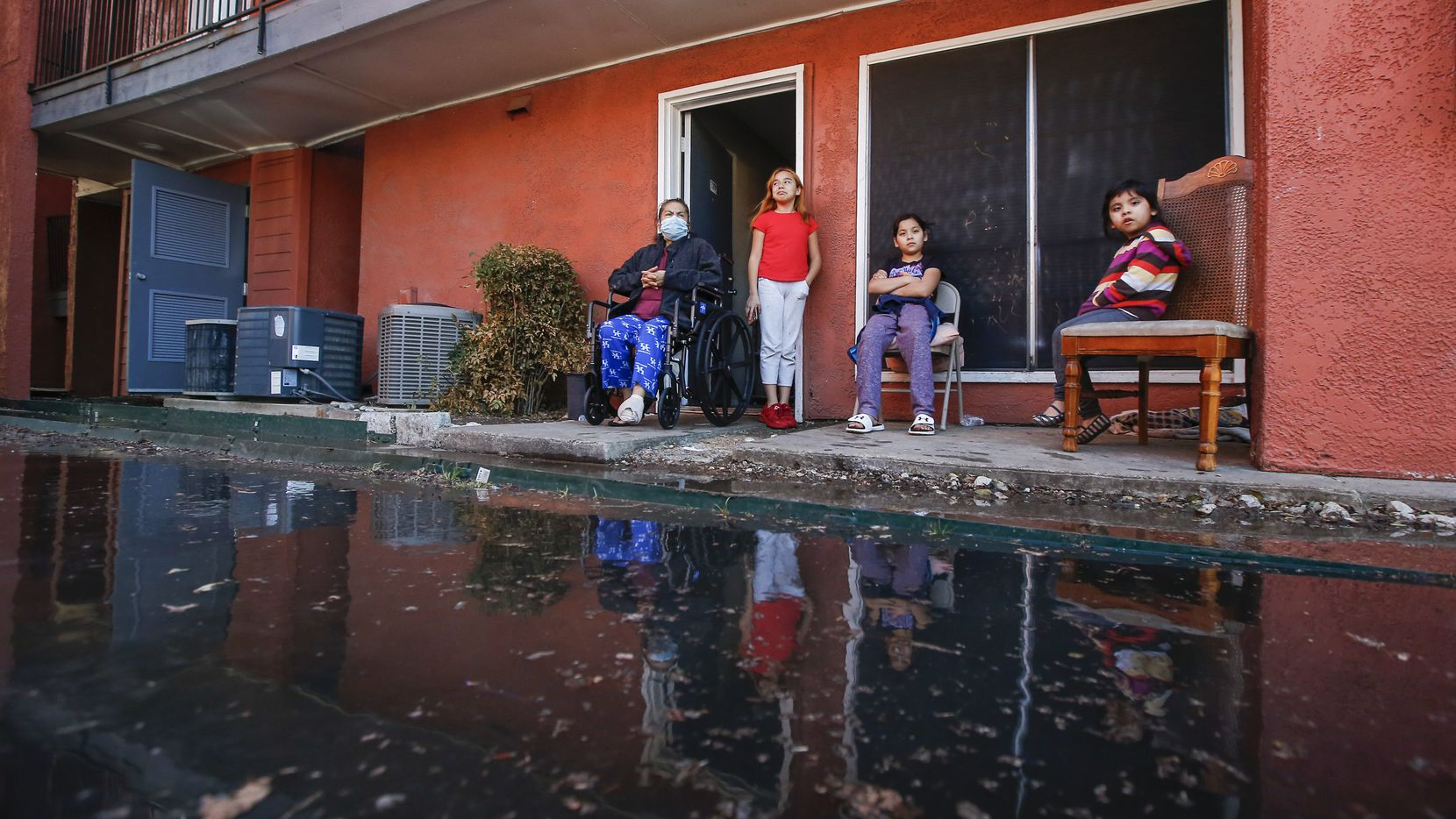 From left: Modesta Gonzalez, 60; Deveany Mendoza, 10; Alina Mendoza, 6; and Guadelupe Mendoza, 4, are reflected in water that flooded their apartment last week at Villas del Solamar in Dallas.