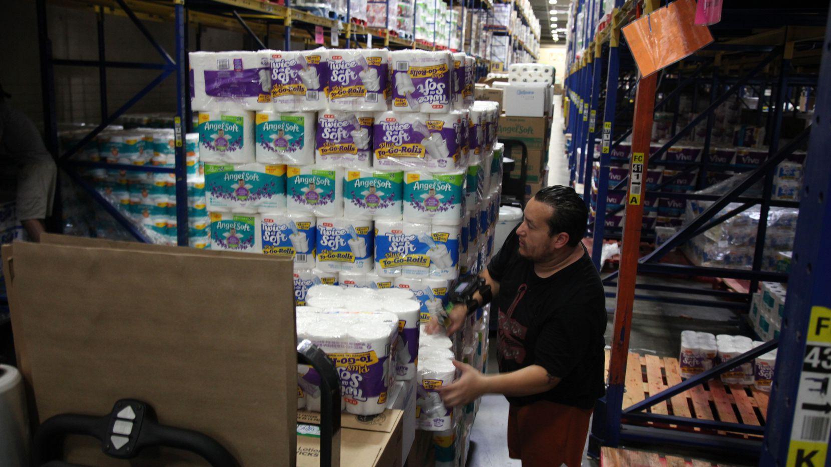 Un empacador de H-E-B en Houston acomada los paquetes de papel higiénico que están en altísima demanda en el estado de Texas. Hay escasez en las tiendas, pero los productores dicen que sí hay suficiente.