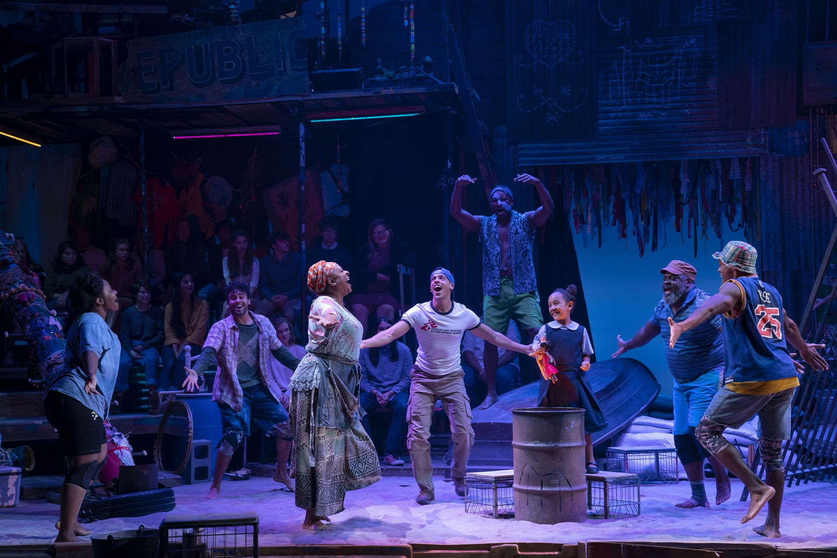 """A scene from the North American touring production of director Michael Arden's 2017 revival of """"Once on This Island."""" Part of the audience sits on stage, real sand beneath their feet, in Arden's immersive version of the 1990 Broadway musical."""