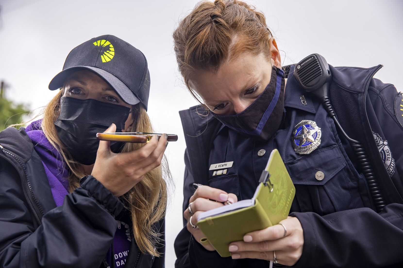 Homeless outreach coordinator Samantha Moran (left) and Dallas police Officer Jennafer Kemph made phone calls to homelessness resource agencies and compared notes as they tried to help an unhoused woman experiencing mental deterioration at The Bridge in downtown Dallas.