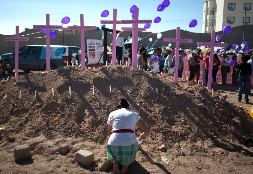 "A woman prays in front of crosses during the passage of the ""caravan of comfort"" along Ciudad Juarez, Chihuahua state, Mexico, on June 10, 2011. Mexicans have erected pink crosses in memory of women killed."