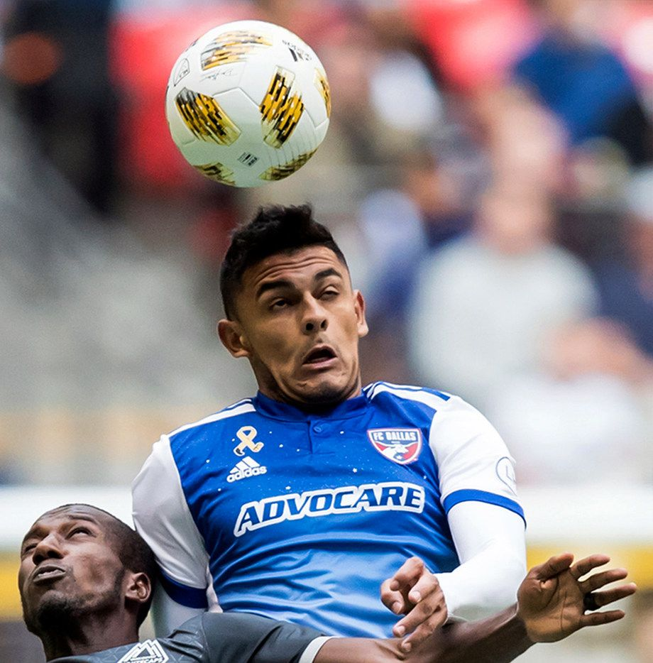 FC Dallas' Cristian Colman, right, gets his head on the ball above Vancouver Whitecaps' Ali Ghazal during the first half of an MLS soccer game in Vancouver, British Columbia, Sunday, Sept. 23, 2018. (Darryl Dyck/The Canadian Press via AP)