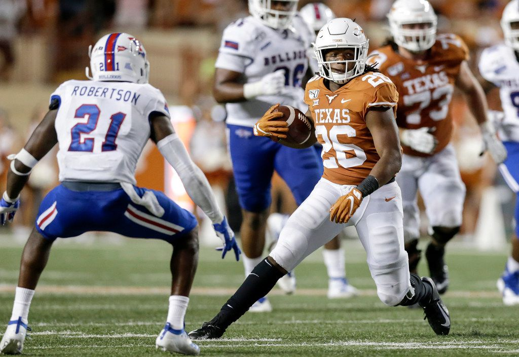 AUSTIN, TX - AUGUST 31:  Keaontay Ingram #26 of the Texas Longhorns runs the ball defended by Amik Robertson #21 of the Louisiana Tech Bulldogs in the third quarter at Darrell K Royal-Texas Memorial Stadium on August 31, 2019 in Austin, Texas.  (Photo by Tim Warner/Getty Images)