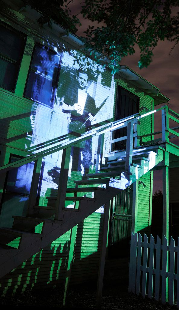 A famous 1963 photo of Lee Harvey Oswald holding a rifle is projected onto the back of the house at 214 W. Neely St. in Dallas, where the picture was taken when Oswald lived there in 1963.