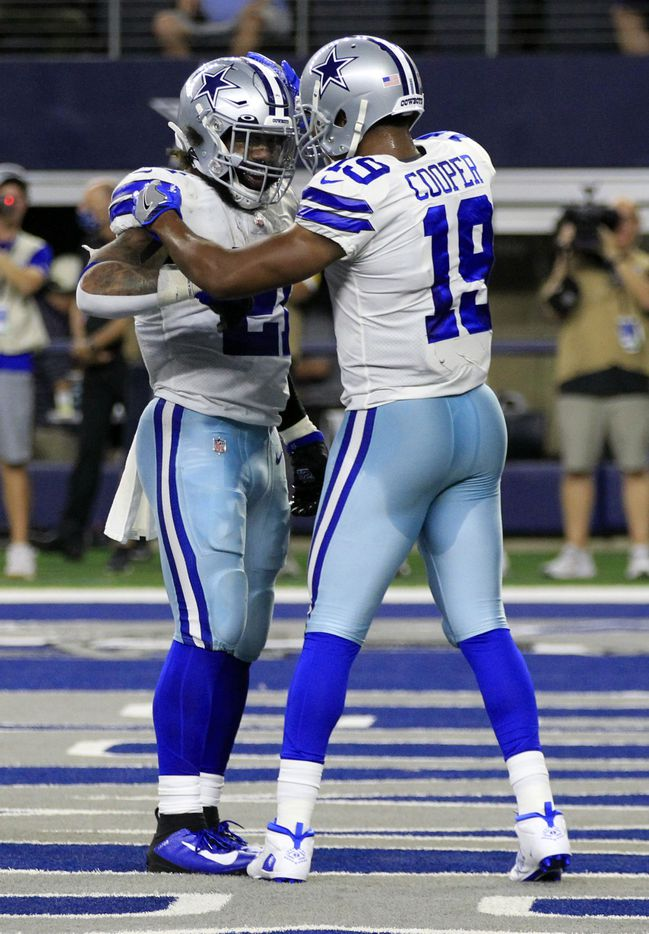 Dallas Cowboys running back Ezekiel Elliott (21) and wide receiver Amari Cooper (19) celebrate after Elliot's touchdown during the first half of a NFL football game between the Dallas Cowboys and the Philadelphia Eagles High at AT&T Stadium in Arlington on Monday, September 27, 2021. (John F. Rhodes / Special Contributor)