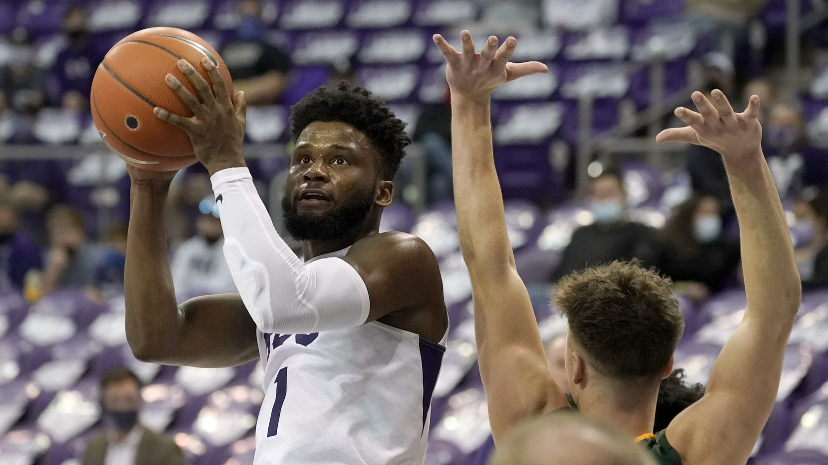 TCU guard Mike Miles (1) looks to the basket as North Dakota State guard Boden Skunberg defends during the second half of an NCAA college basketball game in Fort Worth, Texas, Tuesday, Dec. 22, 2020.