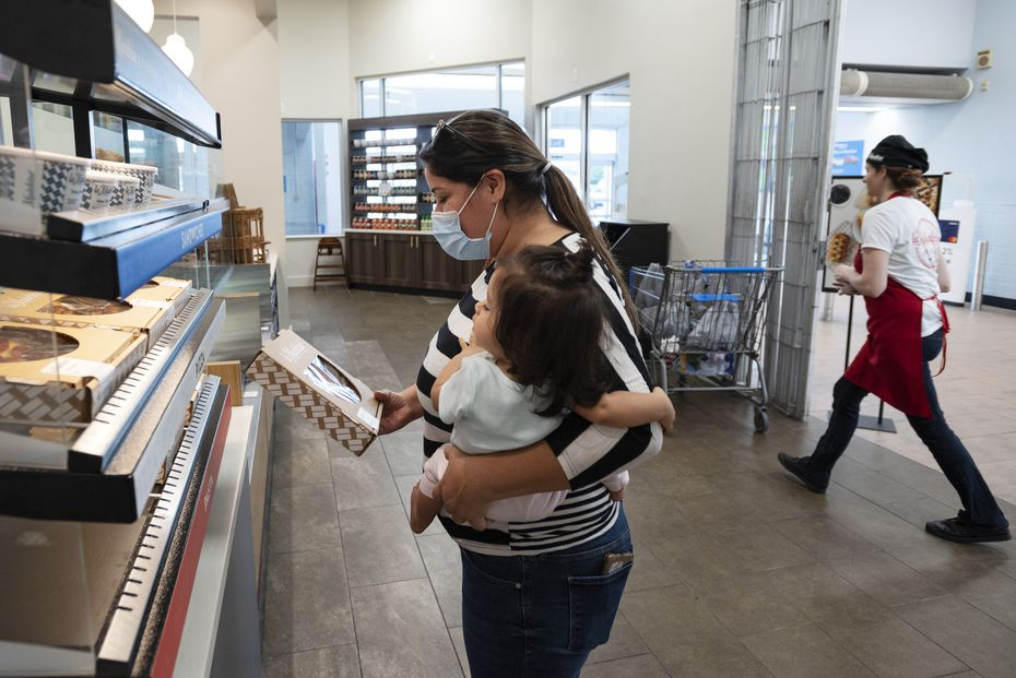 Zaira Garcia holds her baby Liliana Garcia as she picks up a grab-and-go pizza from La Madeleine Express inside the Walmart in Garland.