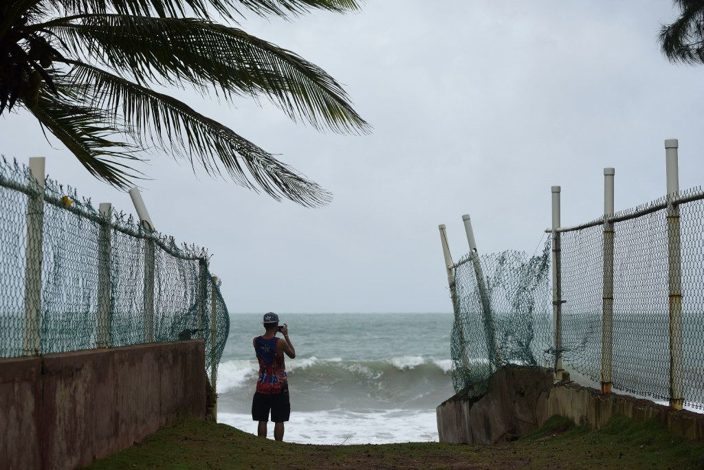 A man photographs the ocean before the arrival of Hurricane Irma, in luquillo, Puerto Rico, on Wednesday. Irma roared into the Caribbean with record force early Wednesday, its 185 mph winds shaking homes and flooding buildings on a chain of small islands along a path toward Puerto Rico, Cuba and Hispaniola and a possible direct hit on densely populated South Florida.