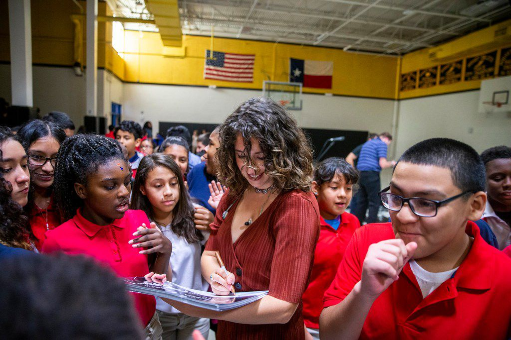 O'Neil signs autographs after performing for the sixth-graders.