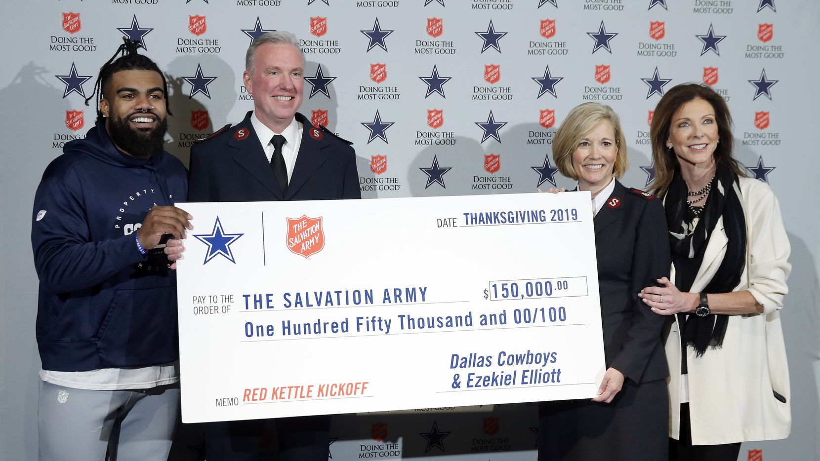 Ahead of the Salvation Army Red Kettle Campaign kickoff, Dallas Cowboys running back Ezekiel Elliott donated proceeds of the 'Zeke Who?' t-shirt to the Salvation Army during a press conference at The Star in Frisco, Texas, Tuesday, November 26, 2019. Joining him (left) with a $150,000 check is Salvation Army's North Texas Area Commanders Major Jon Rich and his wife Barbara Rich, and Cowboys Executive Vice President and Chief Brand Officer Charlotte Jones. (Tom Fox/The Dallas Morning News)