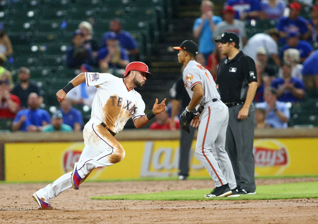 ARLINGTON, TX - JUNE 06: James Hoye #92 umpire looks ones on as Isiah Kiner-Falefa #9 of the Texas Rangers runs last Richie Martin #1 of the Baltimore Orioles to score in the fifth inning at Globe Life Park in Arlington on June 6, 2019 in Arlington, Texas. (Photo by Rick Yeatts/Getty Images)