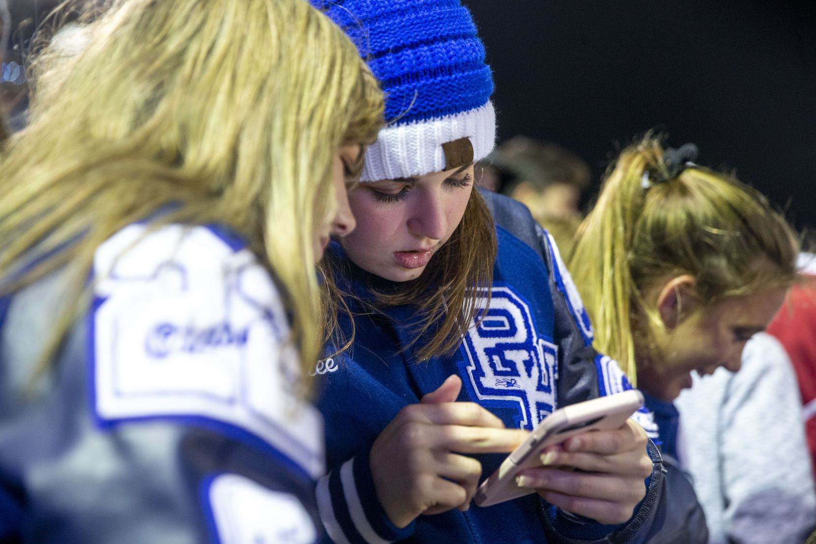Demi Trammell, 16, shows Emalee Maze 15, both of Baytown, a photo on her phone during a football game at Barbers Hill High School on Oct. 25, 2019, in Mont Belvieu. The city added free WiFi to the football stadium as a way to market its internet service, MB Link.