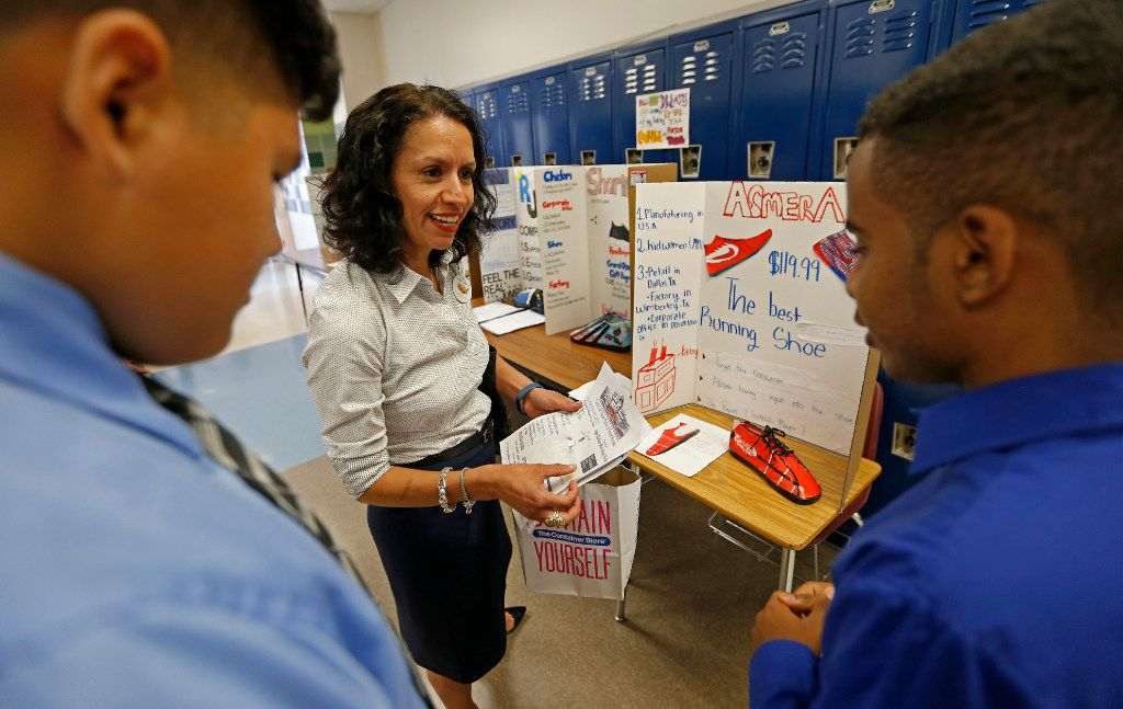 Liz Cedillo-Pereira met with young students at Tasby Middle School who finished an after-school program called Eagle Scholars, in this file photo. She talked with seventh-grader Alessandro Angel (left) and 11th-grader Kudus Weldetensae as they showcased a dream company to make athletic shoes.