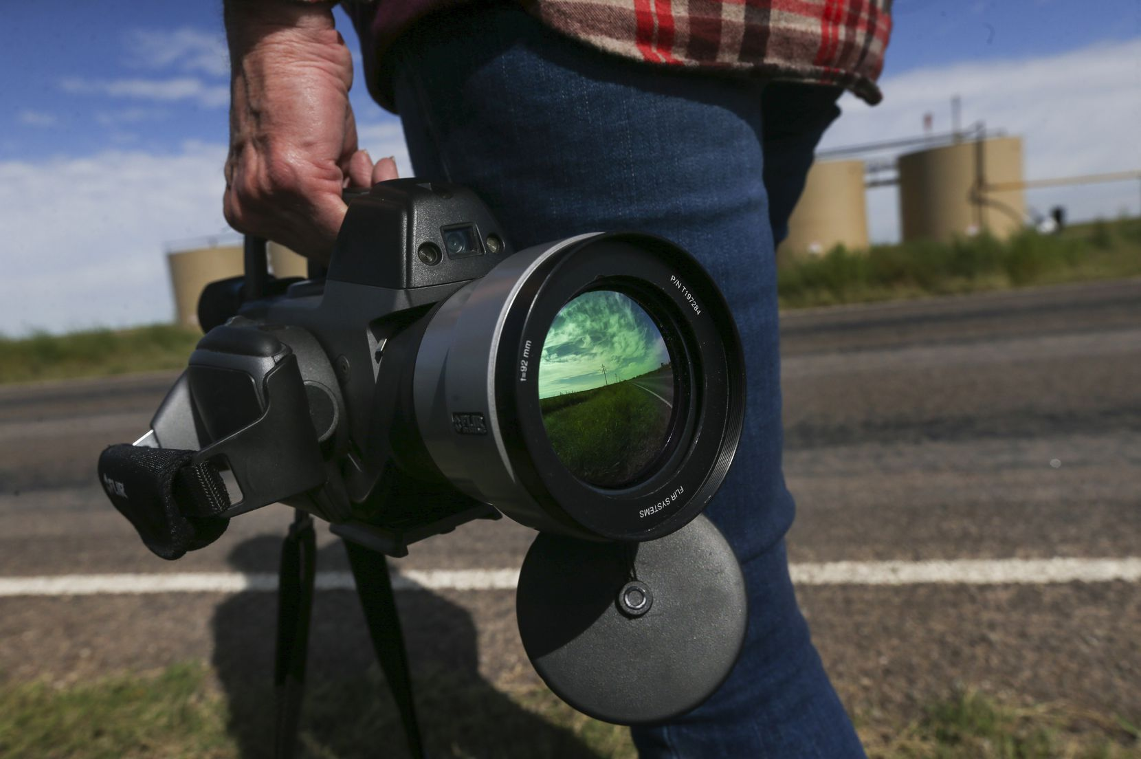 Sharon Wilson clasps a FLIR infrared camera as she prepares to record video of methane and other hydrocarbon emissions from oil storage tanks.