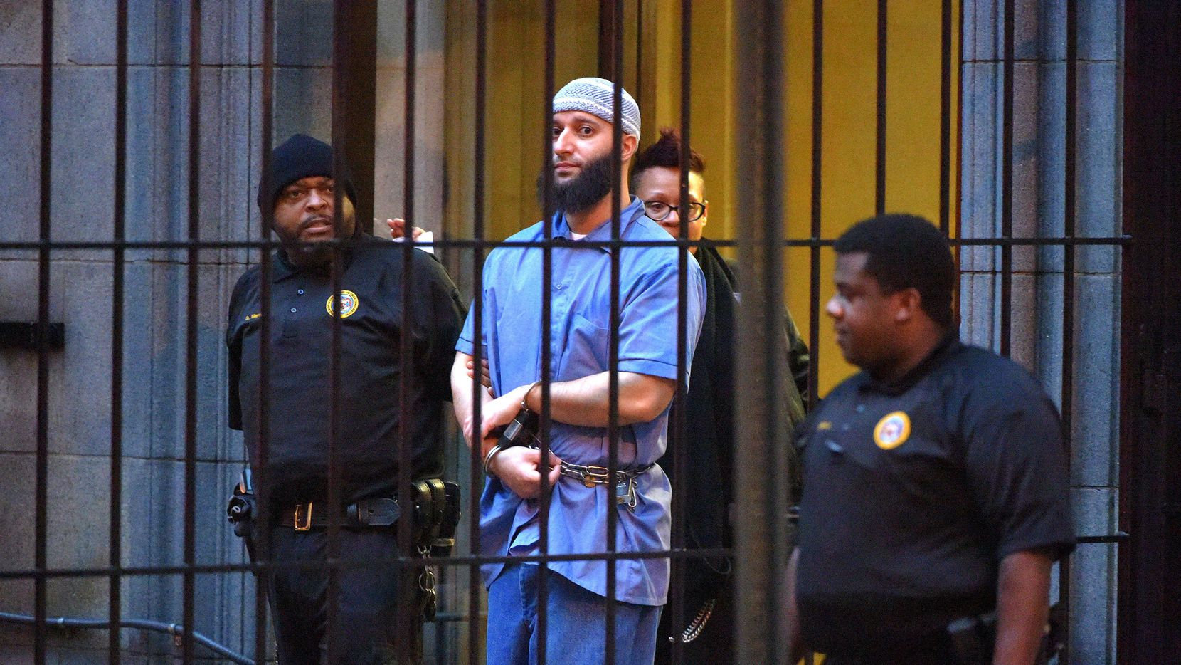 """Officials escort """"Serial"""" podcast subject Adnan Syed from the courthouse on Feb. 3, 2016, following the completion of the first day of hearings for a retrial in Baltimore. Maryland's second-highest court has upheld a judge's ruling overturning the murder conviction of Syed. (Karl Merton Ferron/Baltimore Sun/TNS)"""