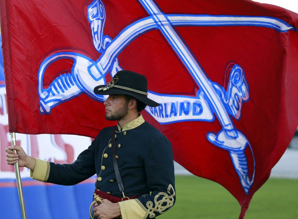 (TXHSFB) South Garland High Colonel Gabriel Valderrama, 17, a senior, holds the school's flag before the start of a football game West Mesquite High on Thursday, September 17, 2015. This month, district trustees decided to remove the Confederate colonel as the school's mascot. (John F. Rhodes / Special Contributor)