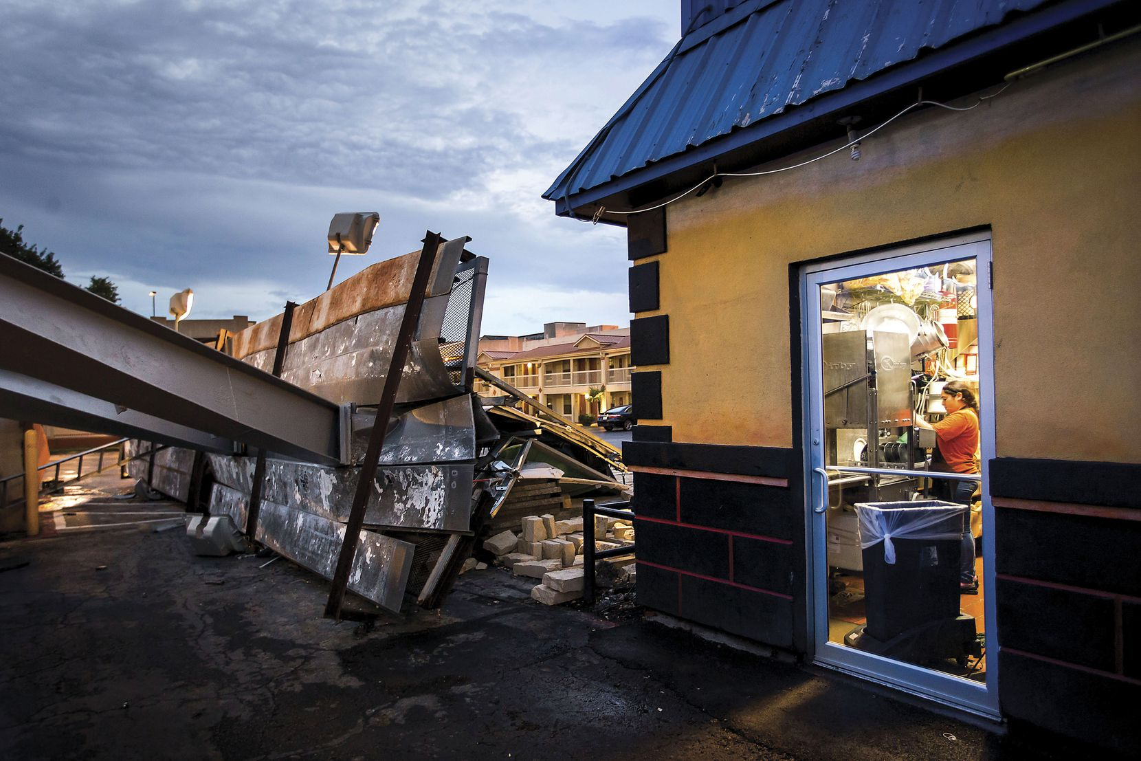 Employees worked in the kitchen of Buzzbrews diner in Dallas on June 27, mere feet away from the spot outside where a billboard was knocked over by storms, crushing a car in the parking lot of the adjacent Best Western Cityplace Inn.