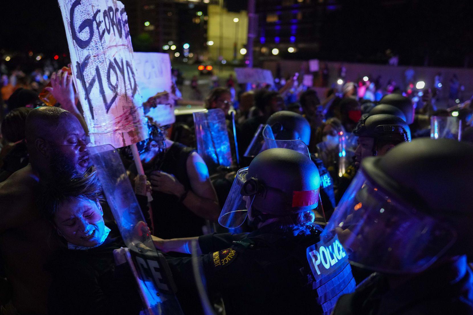 Agentes de la Policía de Dallas tratan de contener el avance de manifestantes en el centro de Dallas, el viernes por la noche.