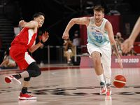 Slovenia's Luka Doncic (77) drives past Japan's Yuta Watanabe (12) in a basketball game during the first half of play at the postponed 2020 Tokyo Olympics at Saitama Super Arena on Thursday, July 29, 2021, in Saitama, Japan. Slovenia defeated Japan 116-81.