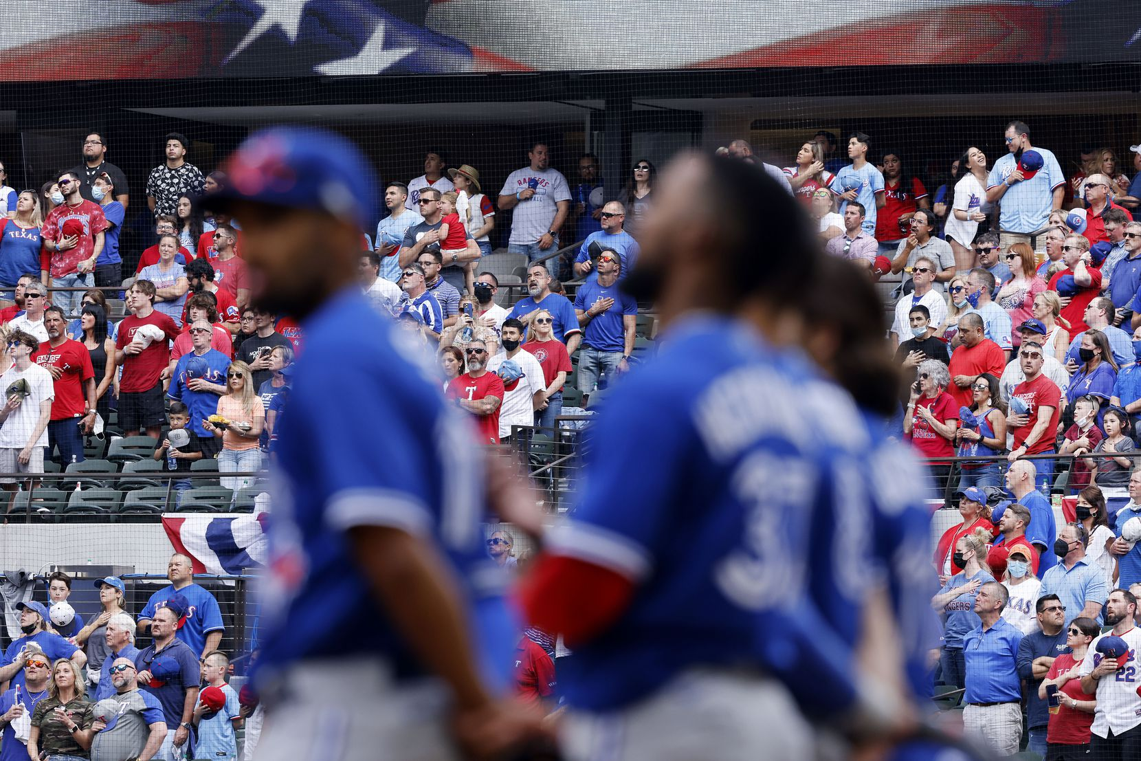 Texas Rangers fans stand and sing God Bless America in the eighth inning as the Toronto Blue Jays players watch at Globe Life Field in Arlington, Monday, April 5, 2021. The Texas Rangers were facing the Toronto Blue Jays in their home opener. (Tom Fox/The Dallas Morning News)