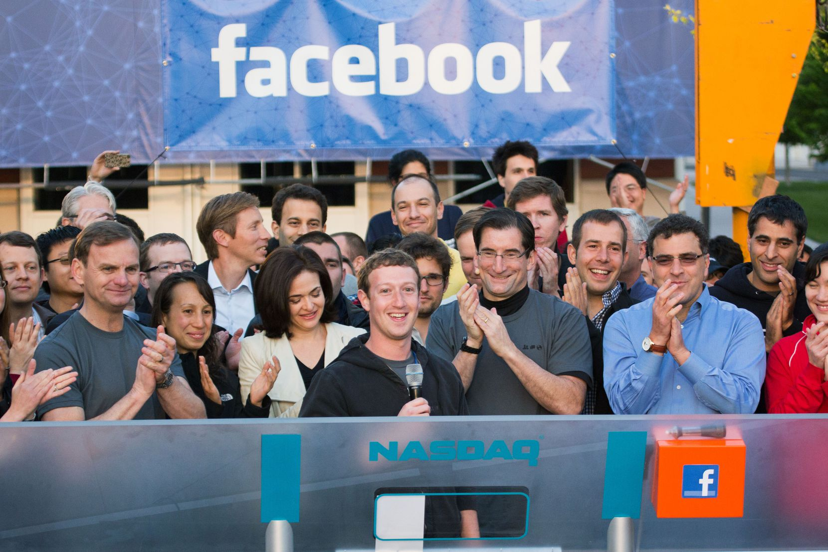 In this image provided by Facebook, Facebook founder, chairman and CEO Mark Zuckerberg, center, rang the opening bell of the Nasdaq stock market on May 18, 2012, from Facebook headquarters in Menlo Park, Calif. The social media company had priced its IPO at $38 per share, and that Friday regular investors got chance to buy shares.